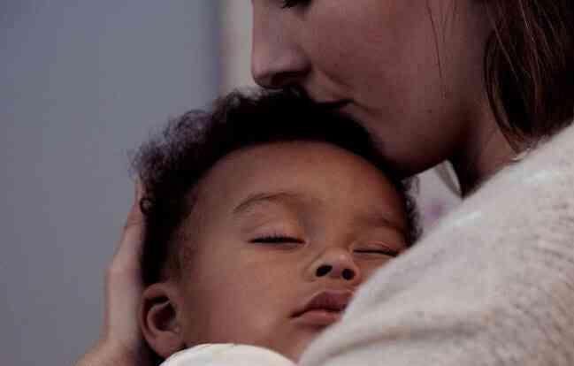 Madre con niño dormido en brazos
